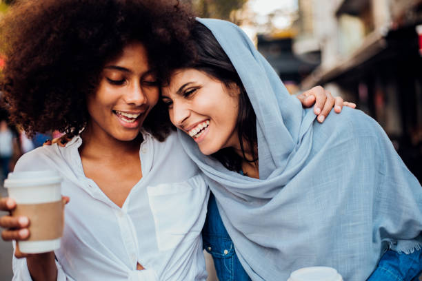 Portrait of the Afro girl and her Arab friend drinking coffee stock photo