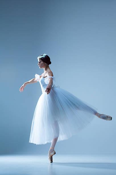 portrait of the ballerina on blue background - beyaz elbise stok fotoğraflar ve resimler