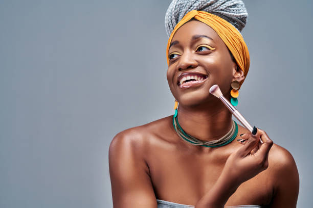 Portrait of the beautiful black woman with make-up brushe near attractive face stock photo