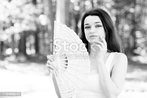 Portrait of the beautiful woman with a fan in a summer garden