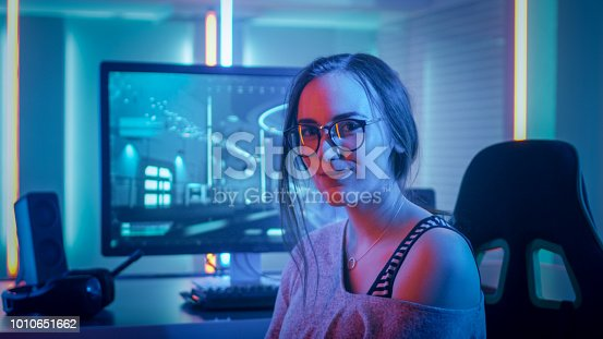 istock Portrait of the Beautiful Young Pro Gamer Girl Sitting at Her Personal Computer and Looks into Camera. Attractive Geek Girl Player Wearing Glasses in the Room Lit by Neon Lights. 1010651662