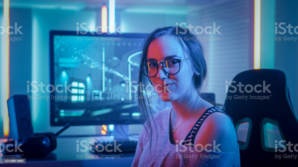 Portrait of the Beautiful Young Pro Gamer Girl Sitting at Her Personal Computer and Looks into Camera. Attractive Geek Girl Player Wearing Glasses in the Room Lit by Neon Lights. stock photo