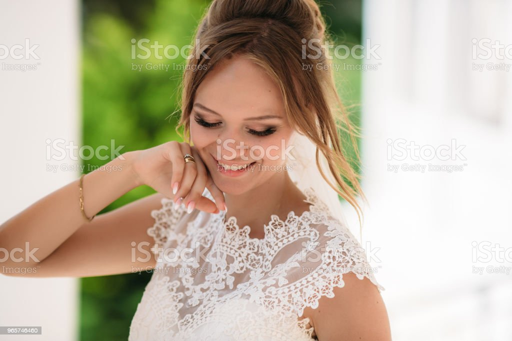 Portrait of the blonde bride, who is having fun and enjoying the wedding day. A girl in nature smiles and shows her beautiful eyes - Royalty-free Adult Stock Photo