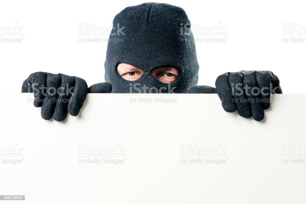 Portrait of the criminal in the mask with a large poster for the inscription stock photo