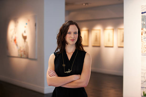 Portrait of the curator A portrait of a young woman standing in front of numerous paintings hanging on the walls of a gallery critic stock pictures, royalty-free photos & images