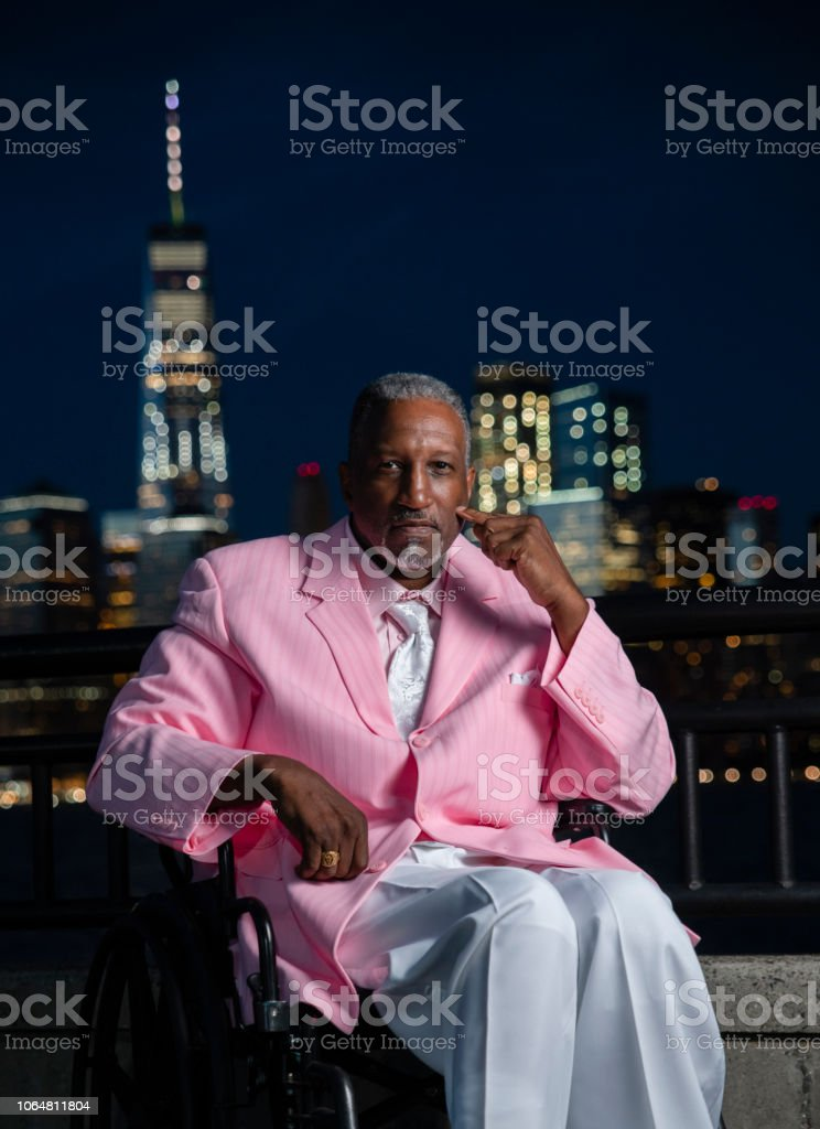 Portrait of the disabled Afro-American Black veteran traveling in America, visiting Liberty State Park in New Jersey. The nigh shot with the illuminated Manhattan Downtown in the backdrop. stock photo