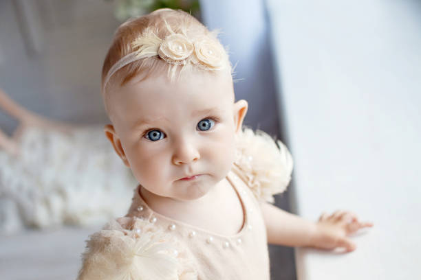 Portrait of the lovely little girl with blue eyes. Serious quiet look stock photo