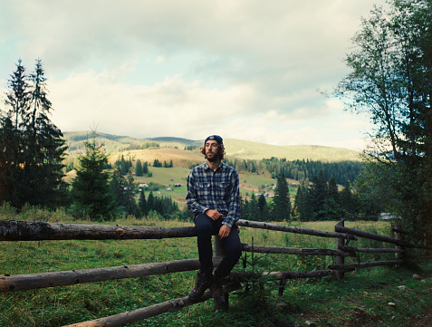 Portrait of the man sitting on the fence in mountains. Camera film