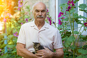 istock Portrait of the old man embracing the little kitten outdoors in the yard 1035978450