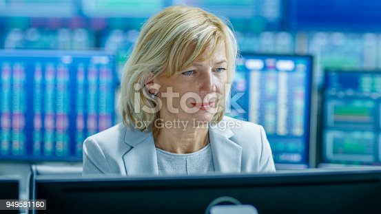 Portrait of the Senior Female Stock Trader Operating at Her Workstation. Behind Her Multiple Monitors Showing Data, Ticker Numbers and Graphs.