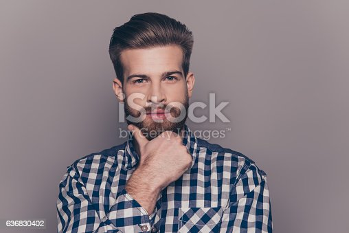 636829368istockphoto portrait of thinking stylish young man touch his beard 636830402