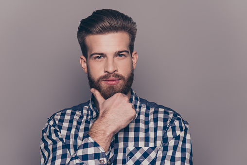 636829368 istock photo portrait of thinking stylish young man touch his beard 636830402