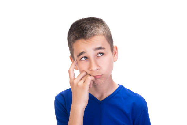 Portrait of thinking teenage boy looking up with curious facial expression against white background