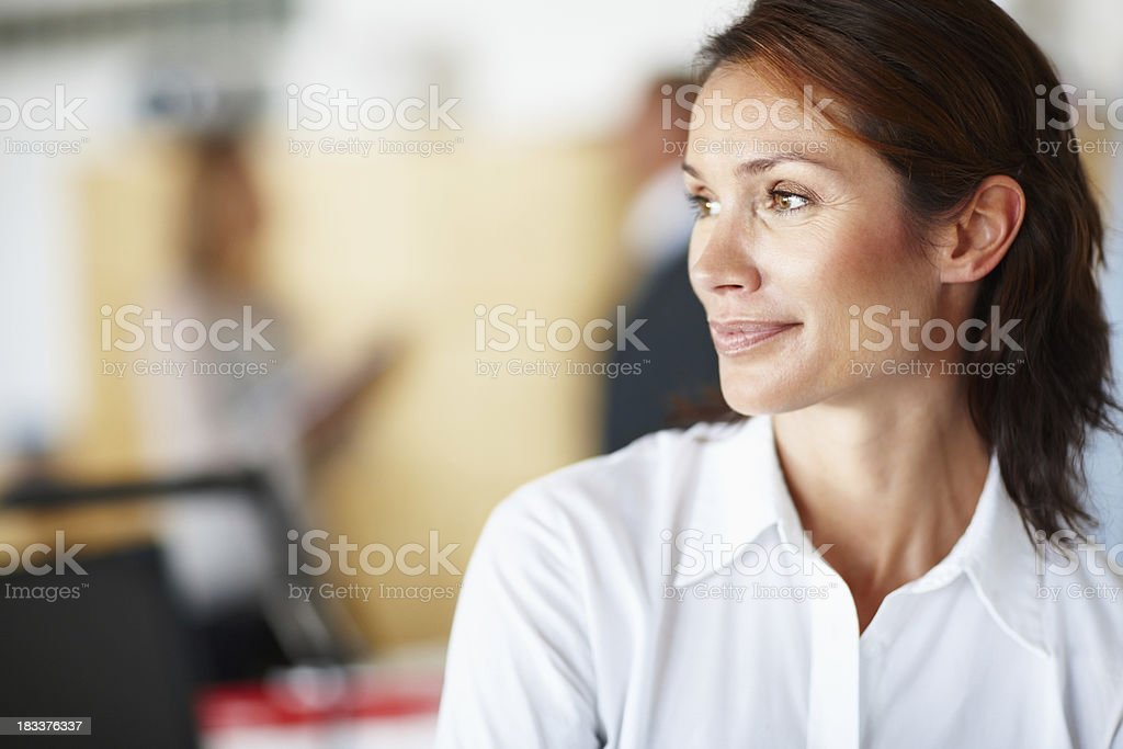 Portrait of thinking woman with coworkers in the background stock photo