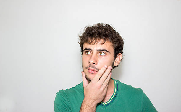 Portrait of thinking young man looking away against gray backgro stock photo