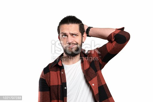 836798276 istock photo Portrait of thinking young man looking up with curious facial expression over white background 1221707233