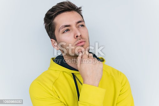 951331990 istock photo Portrait of thoughtful bearded man wearing white T-shirt, looks pensively aside, thinks about his actions and plans for new projects, posing on white studio wall background. People and emotion concept 1093985032