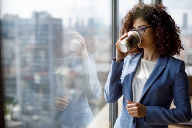 Portrait of thoughtful businesswoman drinking cofee and looking through window stock photo