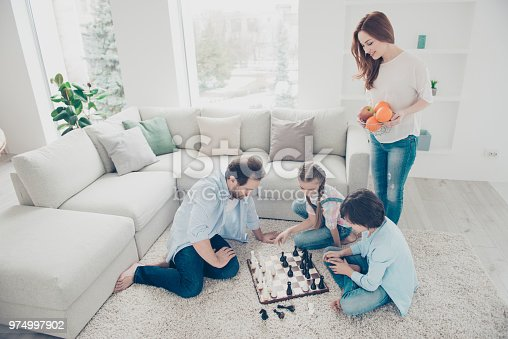 Portrait of thoughtful dad and two kids playing chess board game planning strategy sitting on carpet near sofa, smiling mom bringing plate with fruits for gamers. Idyllic concept