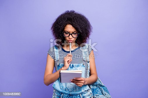 istock Portrait of thoughtful girl holding notepad in hands organizing time planning day learning task preparing for exams isolated on violent background. Additional lessons high-school knowledge concept 1009483992