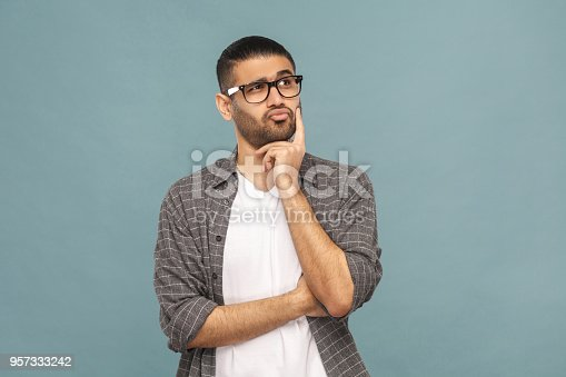 istock Portrait of thoughtful handsome man with black glasses in casual style thinking. 957333242