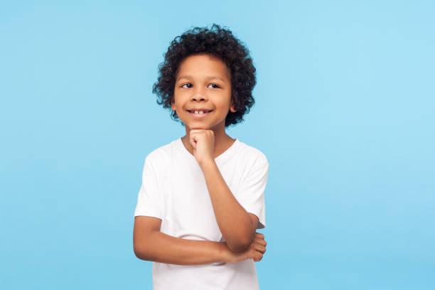 porträtt av tankeväckande glad liten pojke i t-shirt stående med fundersam utseende och röra vid hakan, föreställa sig något roligt och leende - 6 7 år bildbanksfoton och bilder