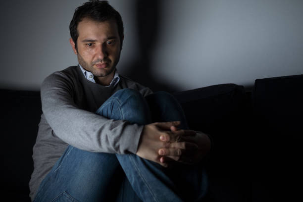 Portrait of thoughtful sad man alone in the dark - foto stock