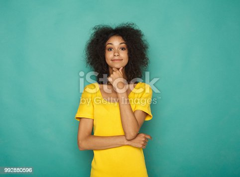 istock Portrait of thoughtful woman with mysterious look 992880596