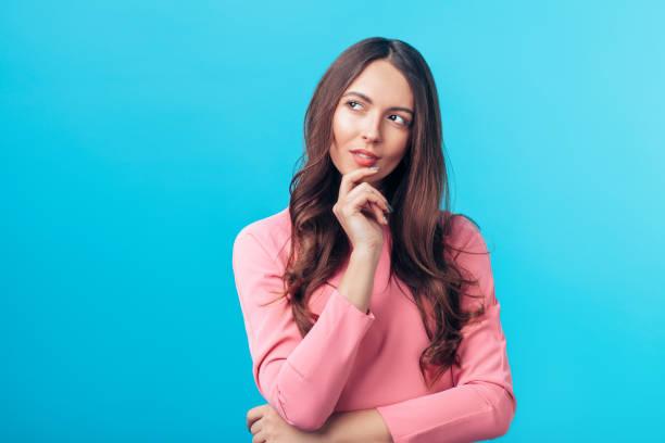 Porträt der nachdenklich staunenden Frau sieht seitlich isoliert über blauen Hintergrund – Foto
