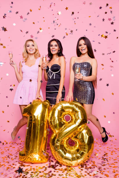 portrait of three attractive, amazing, pretty, astonished, cute models girls having fun,  celebrating  eighteen years old, short dresses with golden balloons and confetti,  standing over pink background - number 18 stock photos and pictures