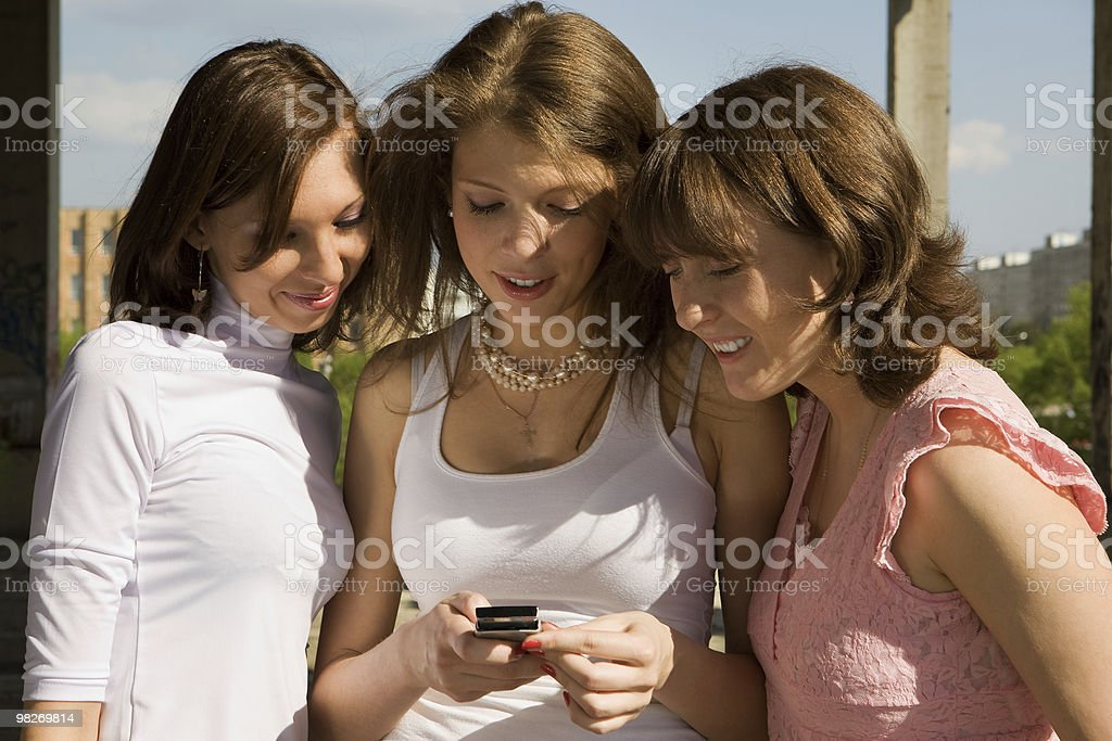 Portrait of three beautiful girls playing around with mobile phone royalty-free stock photo