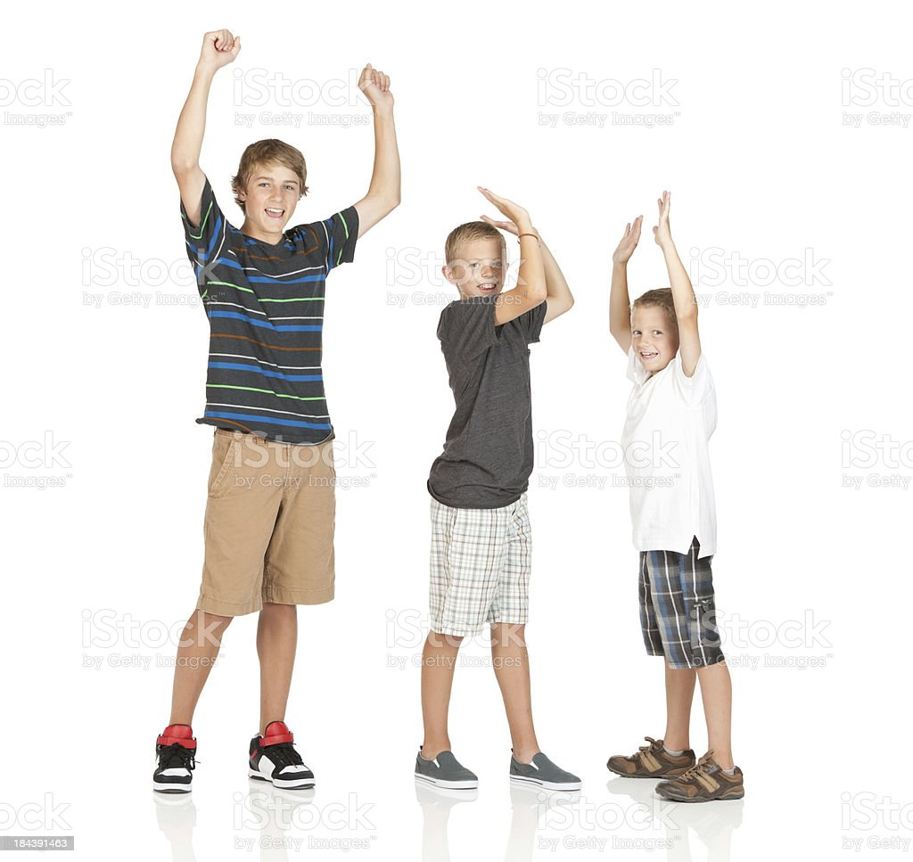 Portrait of three boys standing with their arms raised stock photo