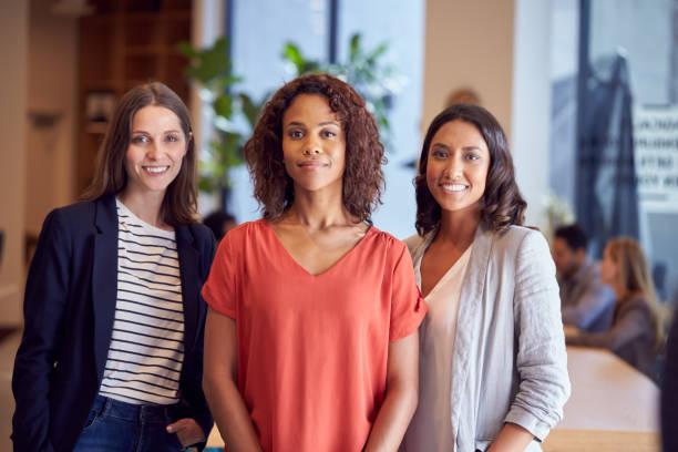 Portrait Of Three Businesswomen Standing In Modern Open Plan Office Together stock photo