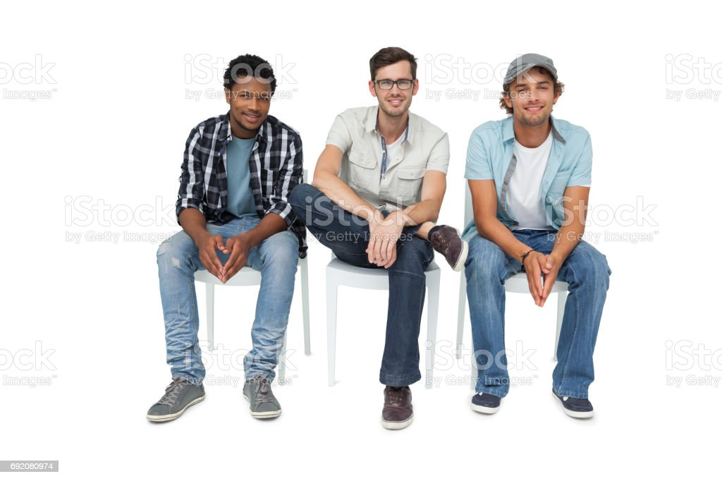 Portrait of three cool young men sitting on chairs stock photo