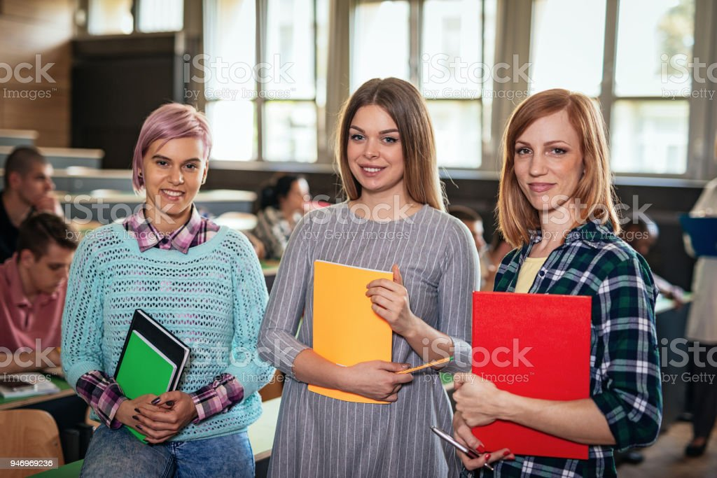 Portrait of three cute students in lecture hall stock photo