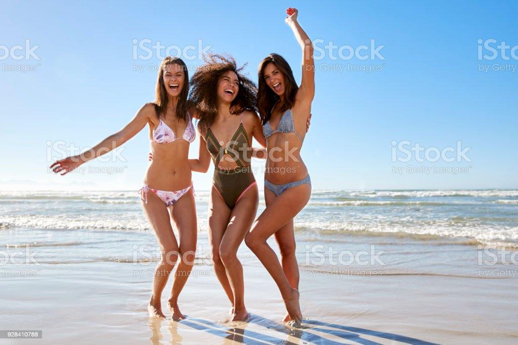 Retrato de tres amigas disfrutando juntos de vacaciones en la playa - foto de stock