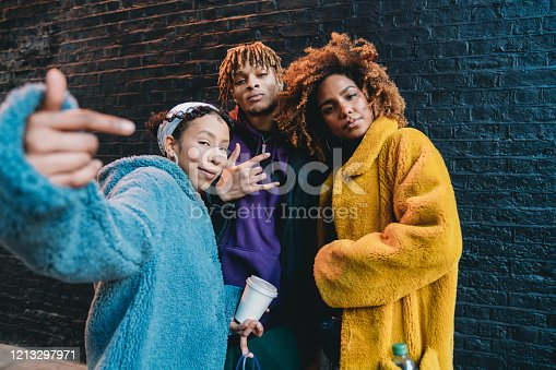 istock Portrait of three friends against a black bricks wall, making gestures in front of the camera 1213297971