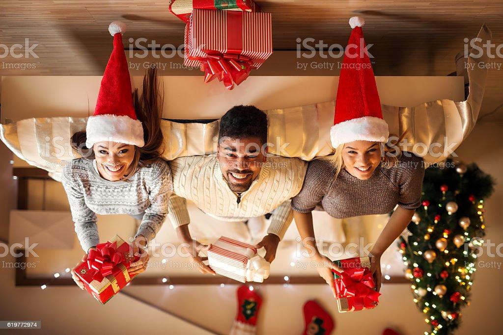 Portrait of three friends lying upside down. stock photo