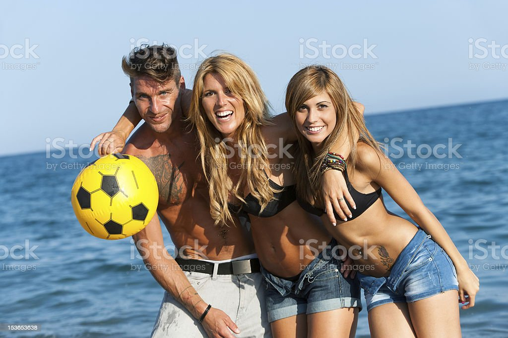 Portrait of three handsome friends on beach. royalty-free stock photo