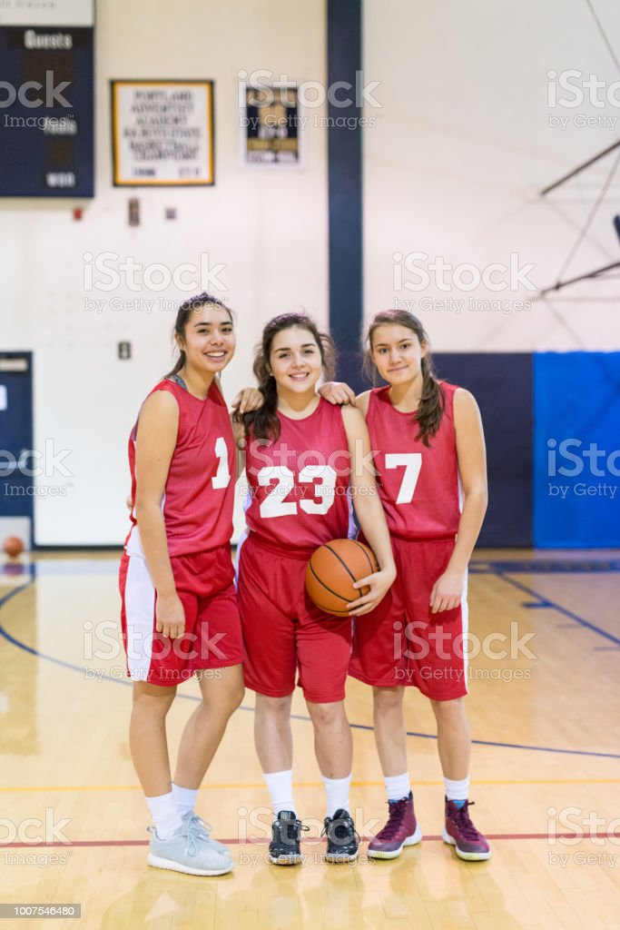 A trio of high school girls pose with each other in their uniforms...