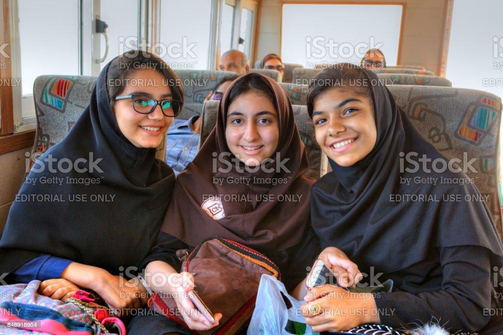 Portrait of three Iranian schoolgirls on board ship, southern Iran. stock photo
