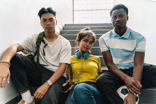 Portrait of three multi ethnic Asian and African teenager students sitting on the Secondary School Staircase