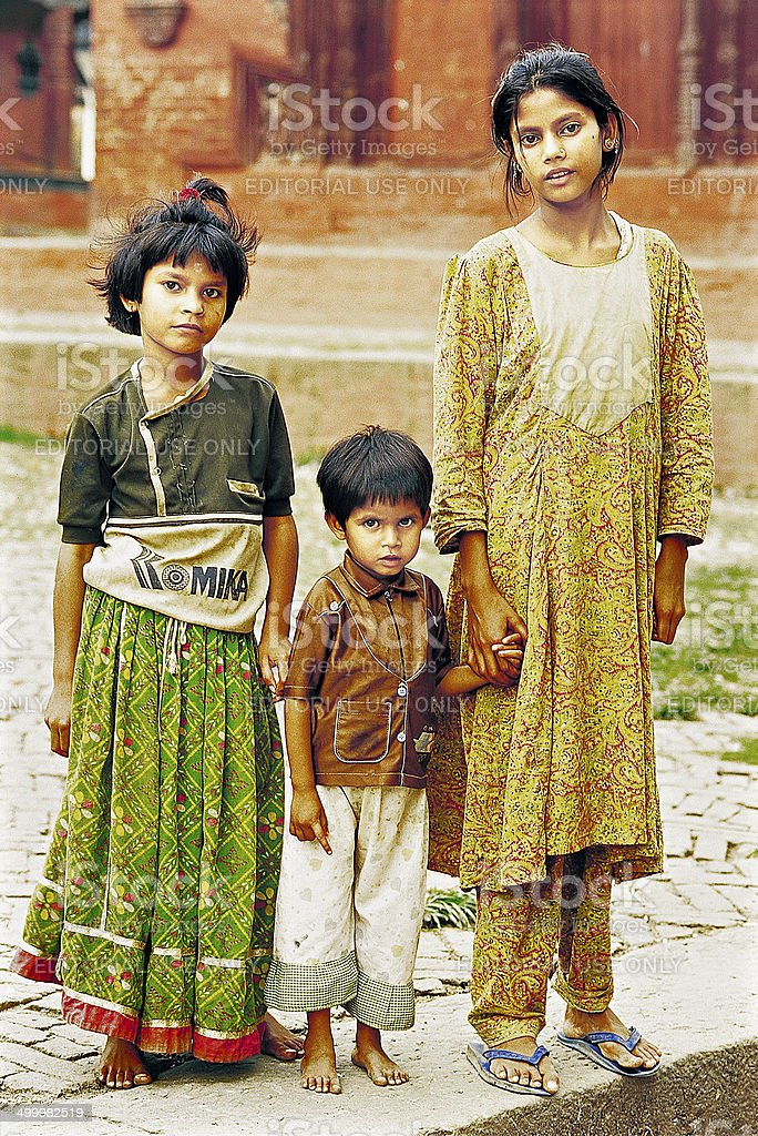 Portrait of three poor kids in typical dresses stock photo