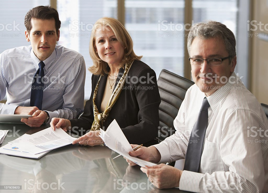 Portrait of three smiling businesspeople in a meeting royalty-free stock photo