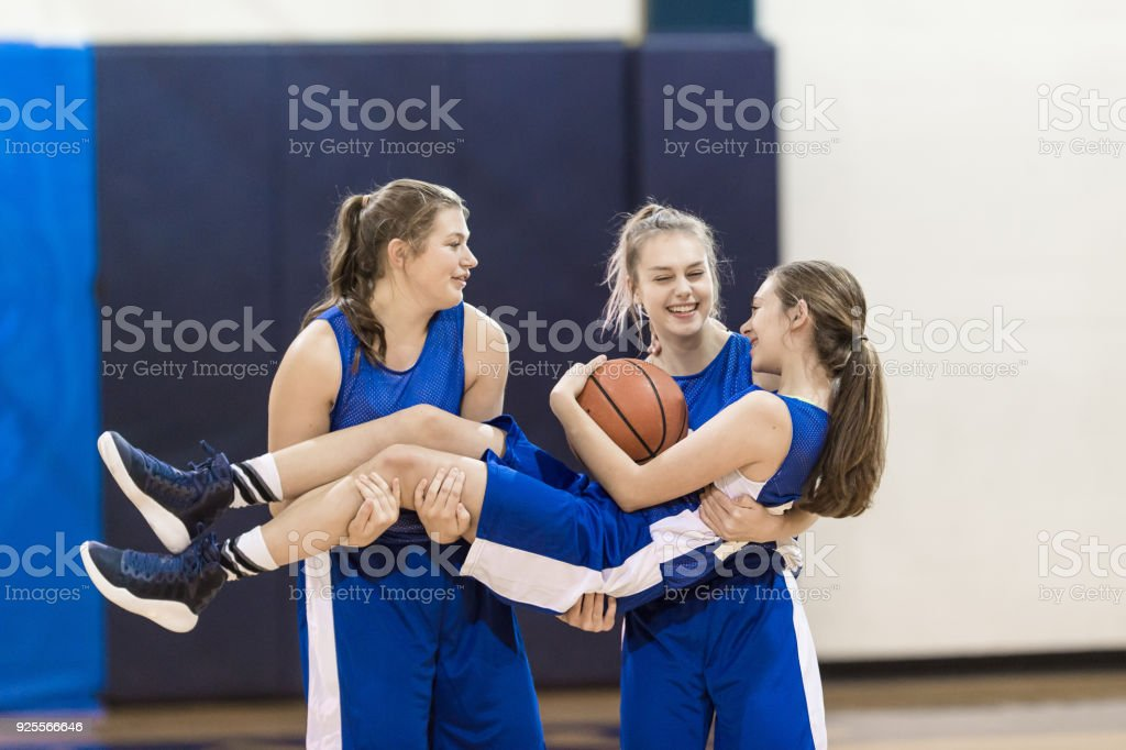 Portrait of three high school basketball players. Two girls are...
