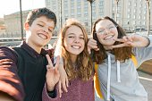 Portrait of three teen friends boy and two girls smiling and taking a selfie outdoors. City background, golden hour.