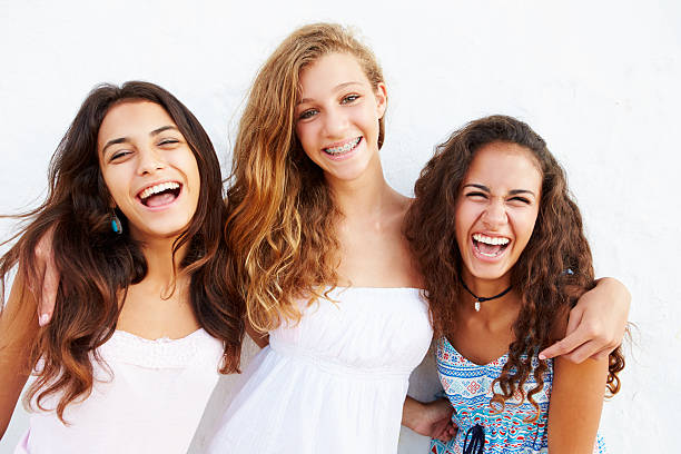 Portrait Of Three Teenage Girls Leaning Against Wall Portrait Of Three Teenage Girls Leaning Against Wall  Smiling To Camera 14 15 years stock pictures, royalty-free photos & images