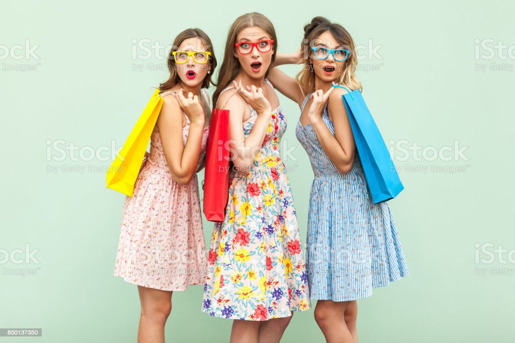 Portrait of three wonder girls with packages and new clothes. stock photo