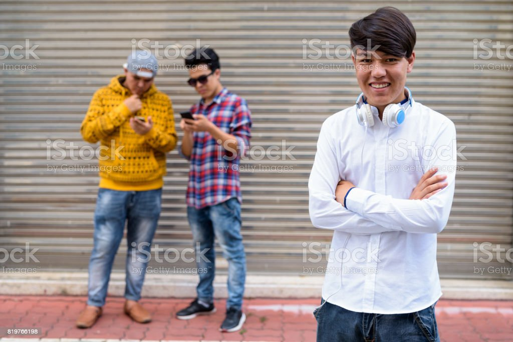 Portrait of three young Asian men standing against warehouse door in Bangkok Thailand stock photo