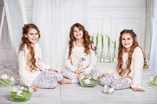 portrait of three young charming sisters - triplets stock photos and pictures